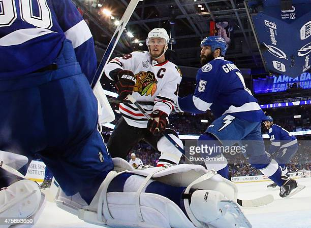 Jonathan Toews of the Chicago Blackhawks skates against Ben Bishop and Jason Garrison of the Tampa Bay Lightning during Game One of the 2015 NHL...
