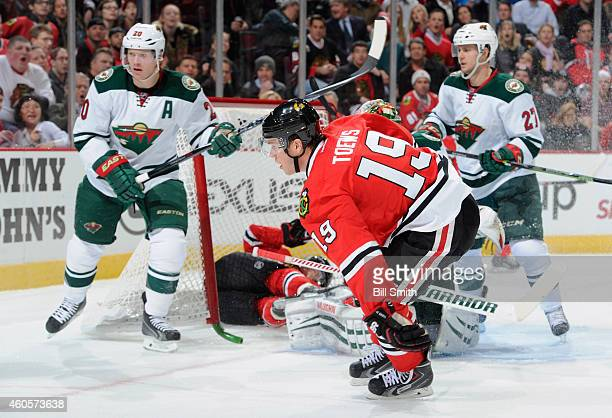 Jonathan Toews of the Chicago Blackhawks skates by Kris Versteeg, who was pushed into the goal, as Ryan Suter and Brett Sutter of the Minnesota Wild...