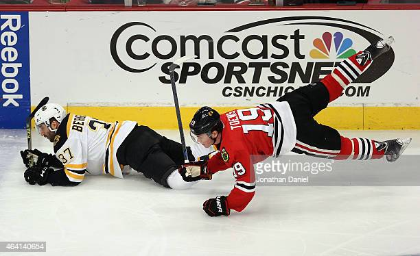 Jonathan Toews of the Chicago Blackhawks slips to the ice while chasing Patrice Bergeron of the Boston Bruins at the United Center on February 22...