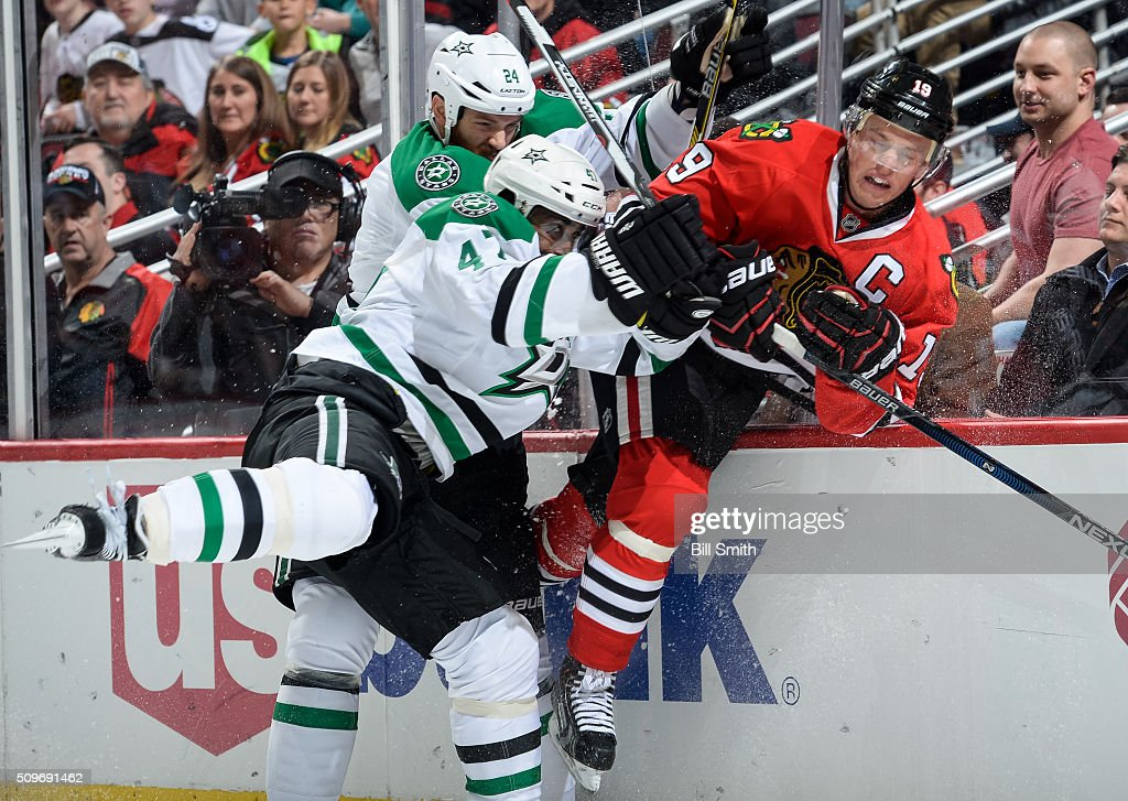 Jonathan Toews #19 of the Chicago Blackhawks takes a hit by Johnny Oduya #47 and Jordie Benn #24 of the Dallas Stars in the third period of the NHL game at the United Center on February 11, 2016 in Chicago, Illinois.
