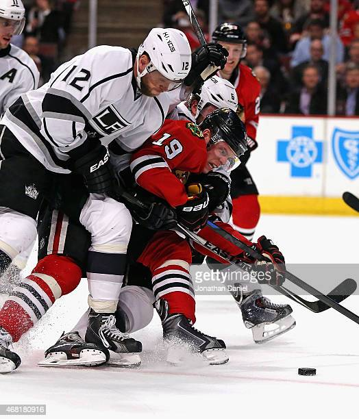 Jonathan Toews of the Chicago Blackhawks tries to get off a shot as he's squeezed by Marian Gaborik and Jake Muzzin of the Los Angeles Kings at the...
