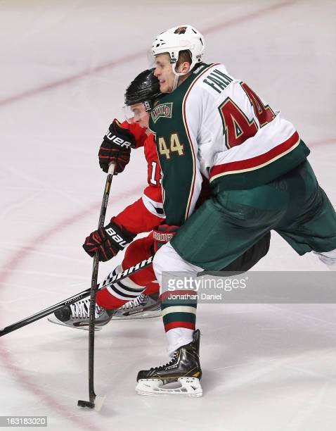 Jonathan Toews of the Chicago Blackhawks tries to get off a shot under pressure from Justin Falk of the Minnesota Wild at the United Center on March...