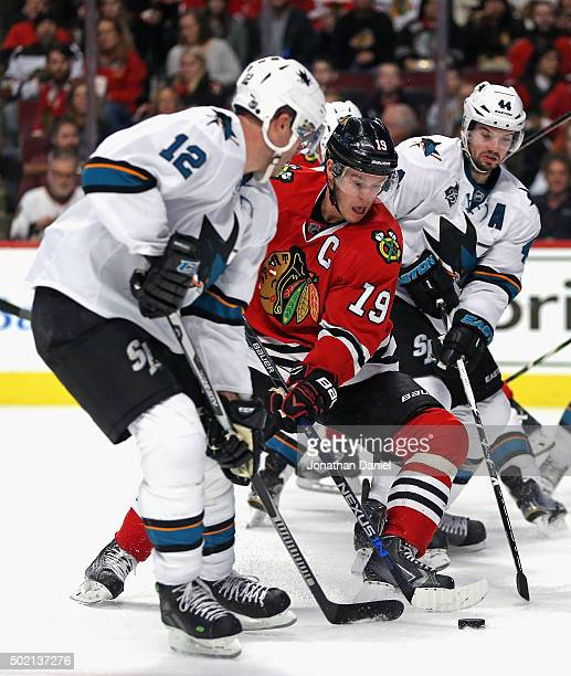 Jonathan Toews of the Chicago Blackhawks tries to get off a shot between Patrick Marleau and MarcEdouard Vlasic of the San Jose Sharks at the United...