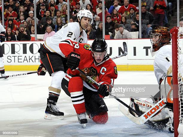 Jonathan Toews of the Chicago Blackhawks tries to get the puck past goalie Jonas Hiller of the Anaheim Ducks as Scott Niedermayer of the Ducks pushes...