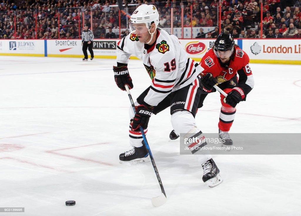 Jonathan Toews #19 of the Chicago Blackhawks uses his body to keep the p[uck from Erik Karlsson #65 of the Ottawa Senators at Canadian Tire Centre on January 9, 2018 in Ottawa, Ontario, Canada.