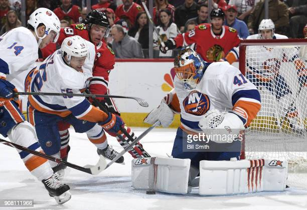 Jonathan Toews of the Chicago Blackhawks works to get at the puck against Tanner Fritz and Thomas Hickey of the New York Islanders next to goalie...
