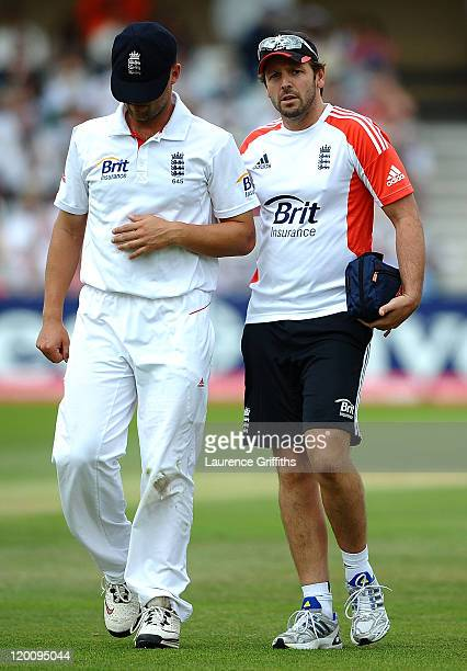 Jonathan Trott of England walks off the field clutching his shoulder with Physio Ben Langley during the second npower Test match between England and...