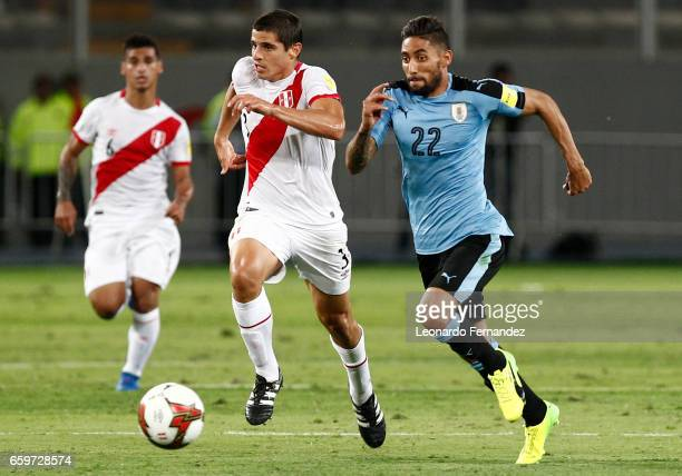 Jonathan Urretaviscaya of Uruguay struggles for the ball with Aldo Corzo of Peru during a match between Peru and Uruguay as part of FIFA 2018 World...