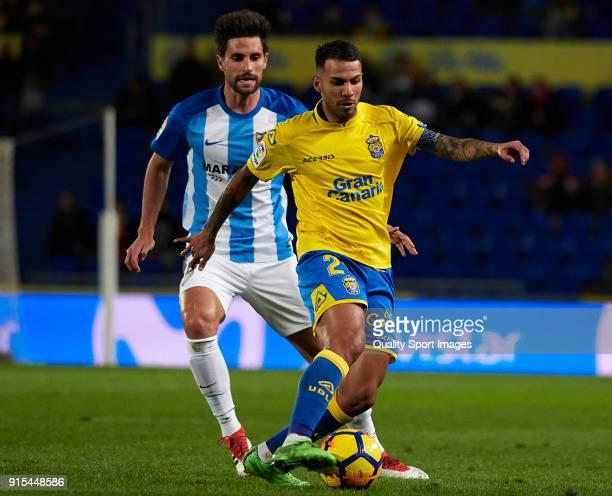 Jonathan Viera of Las Palmas competes for the ball with Adrian Gonzalez of Malaga during the La Liga match between Las Palmas and Malaga at Estadio...