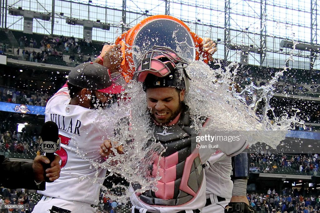 Jonathan Villar #5 and Hernan Perez #14 of the Milwaukee Brewers dump water on Manny Pina #9 after defeating the New York Mets 11-9 at Miller Park on May 14, 2017 in Milwaukee, Wisconsin. Players are wearing pink to celebrate Mother's Day weekend and support breast cancer awareness.