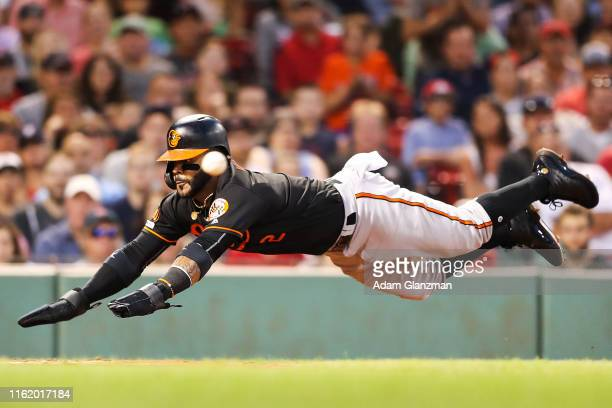 Jonathan Villar of the Baltimore Orioles scores as he dives head first into home plate past the incoming ball in the third inning of a game against...
