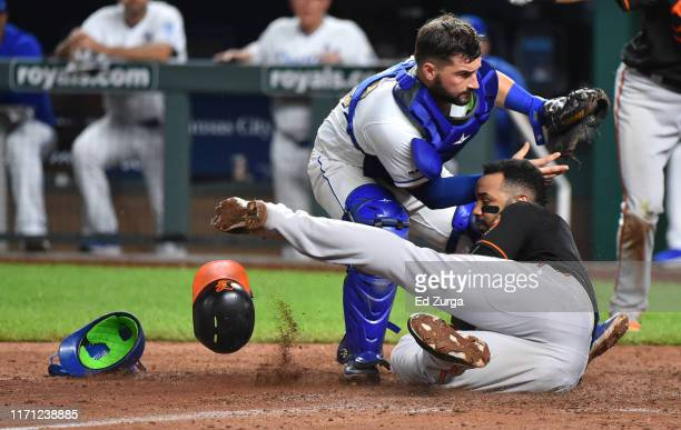 Jonathan Villar of the Baltimore Orioles scores while stealing home against catcher Nick Dini of the Kansas City Royals in the seventh inning at...
