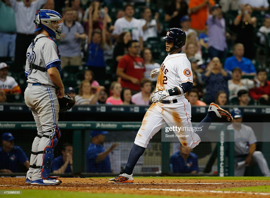 Jonathan Villar #2 of the Houston Astros scores a run as Josh Thole #22 of the Toronto Blue Jays looks on in the seventh inning of their game at Minute Maid Park on May 14, 2015 in Houston, Texas.
