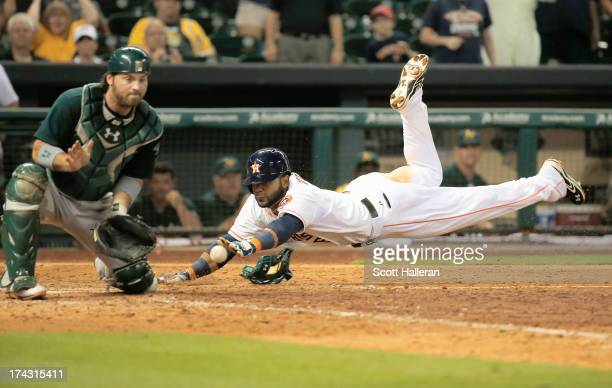 Jonathan Villar of the Houston Astros scores the winning run in the ninth inning as John Jaso of the Oakland Athletics looks on at Minute Maid Park...