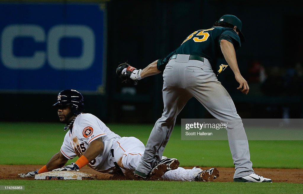Jonathan Villar #6 of the Houston Astros steals second base in the third inning under the tag of Grant Green #35 of the Oakland Athletics at Minute Maid Park on July 22, 2013 in Houston, Texas.