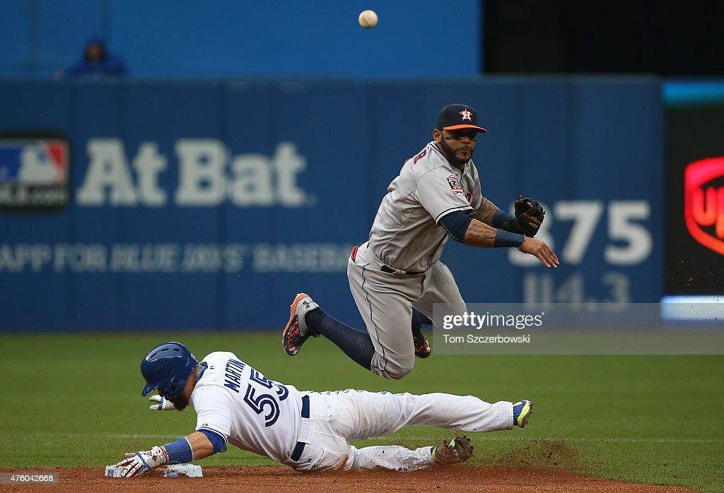 Jonathan Villar #2 of the Houston Astros turns a double play in the second inning during MLB game action as Russell Martin #55 of the Toronto Blue Jays slides into second base on June 5, 2015 at Rogers Centre in Toronto, Ontario, Canada.
