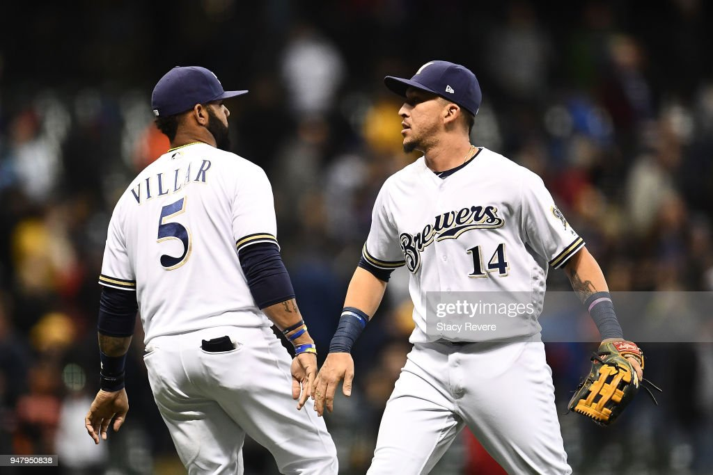 Jonathan Villar #5 of the Milwaukee Brewers and Hernan Perez #14 celebrate a 2-0 victory over the Cincinnati Reds at Miller Park on April 17, 2018 in Milwaukee, Wisconsin.