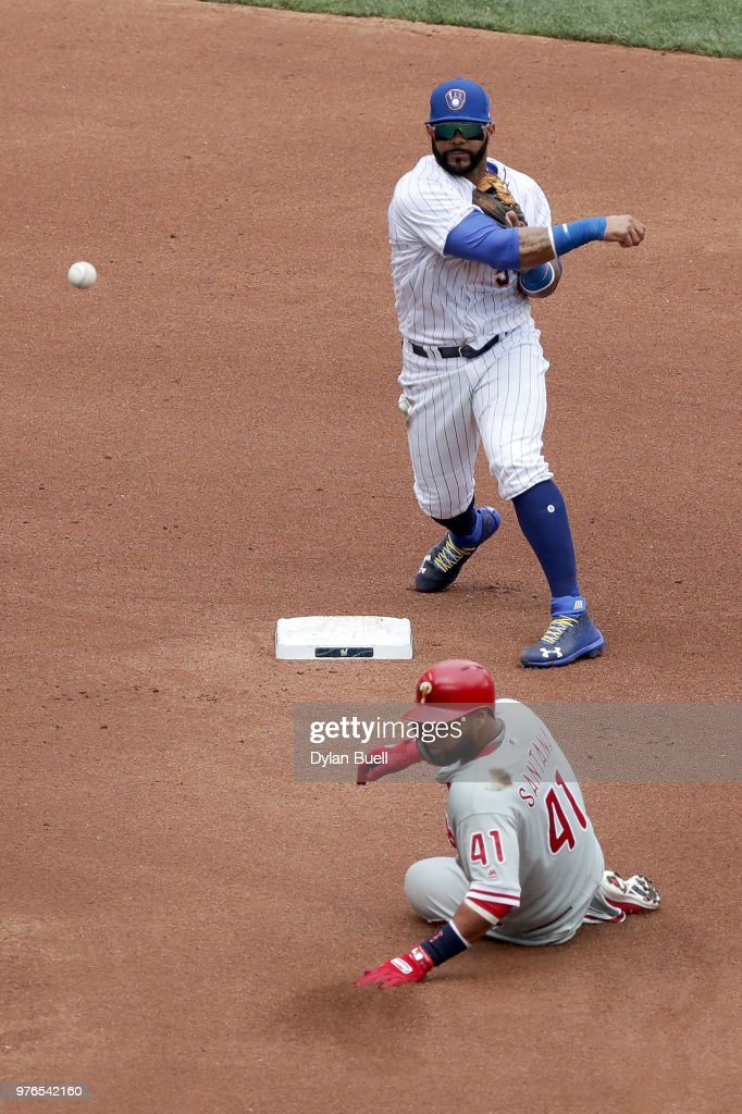 Jonathan Villar #5 of the Milwaukee Brewers attempts to turn a double play past Carlos Santana #41 of the Philadelphia Phillies in the fourth inning at Miller Park on June 16, 2018 in Milwaukee, Wisconsin.