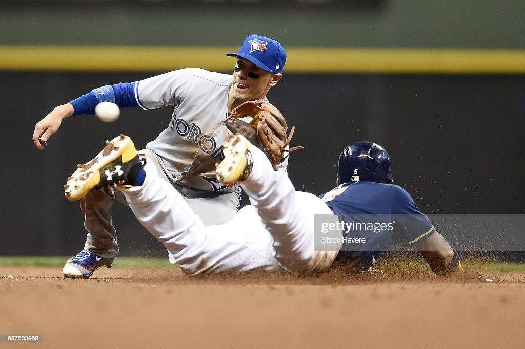Jonathan Villar #5 of the Milwaukee Brewers beats the tag at second base from Ryan Goins #17 of the Toronto Blue Jays during the seventh inning of a game at Miller Park on May 23, 2017 in Milwaukee, Wisconsin.