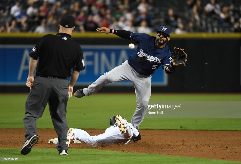Jonathan Villar #5 of the Milwaukee Brewers makes a play on a wild throw as Jarrod Dyson #1 of the Arizona Diamondbacks safely slides into second base during the third inning at Chase Field on May 16, 2018 in Phoenix, Arizona.