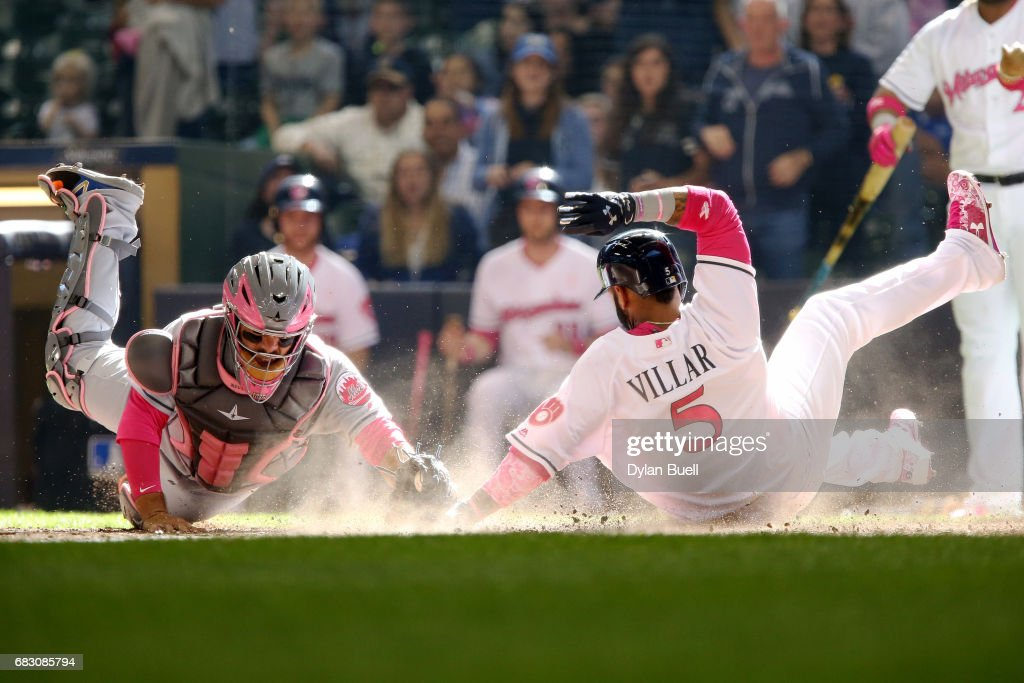 Jonathan Villar #5 of the Milwaukee Brewers slides into home plate to score a run past Rene Rivera #44 of the New York Mets in the eighth inning at Miller Park on May 14, 2017 in Milwaukee, Wisconsin. Players are wearing pink to celebrate Mother's Day weekend and support breast cancer awareness.