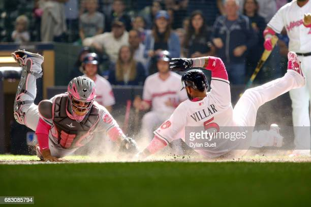 Jonathan Villar of the Milwaukee Brewers slides into home plate to score a run past Rene Rivera of the New York Mets in the eighth inning at Miller...