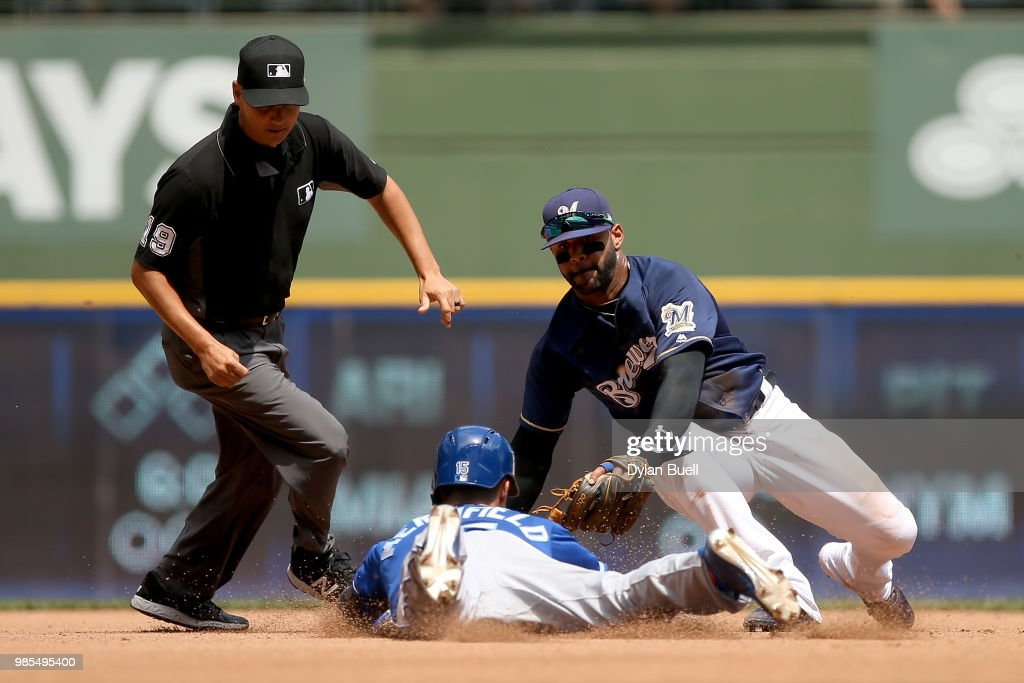 Jonathan Villar #5 of the Milwaukee Brewers tags out Whit Merrifield #15 of the Kansas City Royals at second base in the sixth inning at Miller Park on June 27, 2018 in Milwaukee, Wisconsin.