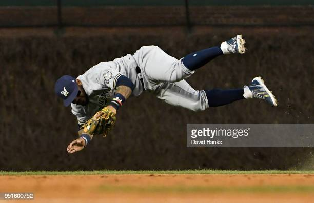 Jonathan Villar of the Milwaukee Brewers tries to make a play on an infield single hit by Addison Russell of the Chicago Cubs during the second...