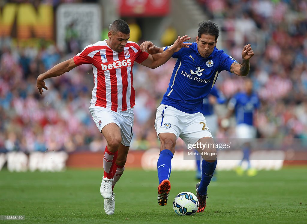 Jonathan Walters of Stoke City and Leonardo Ulloa of Leicester City battle for the ball during the Barclays Premier League match between Stoke City and Leicester City at Britannia Stadium on September 13, 2014 in Stoke on Trent, England.
