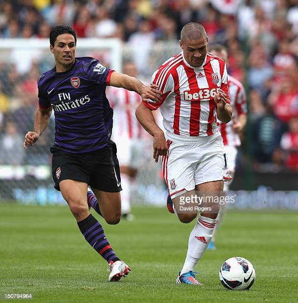 Jonathan Walters of Stoke City moves away from Mikel Arteta during the Barclays Premier League match between Stoke City and Arsenal at the Britannia...