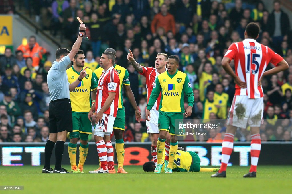 Jonathan Walters of Stoke is shown the red card by referee Andre Marriner following his challenge on Alexander Tettey #27 of Norwich during the Barclays Premier League match between Norwich and Stoke at Carrow Road on March 8, 2014 in Norwich, England.