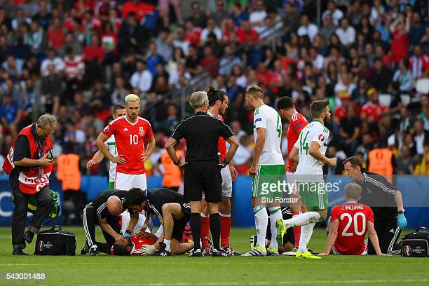 Jonathan Williams and Ashley Williams of Wales receive medical treatment on the pitch after their collision while Northern Ireland players protest...