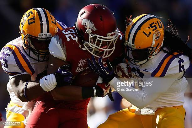 Jonathan Williams of the Arkansas Razorbacks is tackled by Kwon Alexander and Craig Loston of the LSU Tigers at Tiger Stadium on November 29 2013 in...