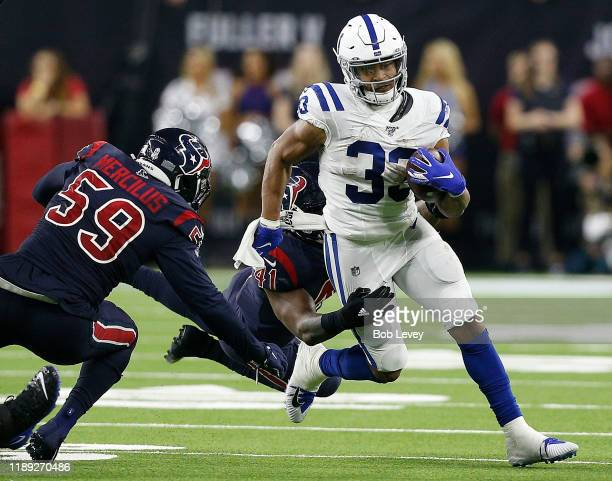 Jonathan Williams of the Indianapolis Colts is tackled from behind from Zach Cunningham of the Houston Texans as Whitney Mercilus assists during the...