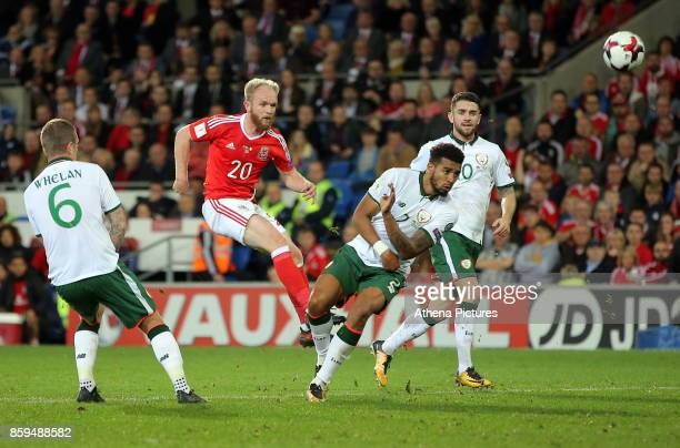 Jonathan Williams of Wales shoots the ball off target while closely marked by Glenn Whelan and Cyrus Christie of Ireland during the FIFA World Cup...