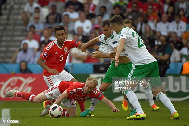 Jonathan Williams#20 of Wales battles for the ball with Northern Ireland players during the UEFA EURO 2016 round of 16 match between Wales and...