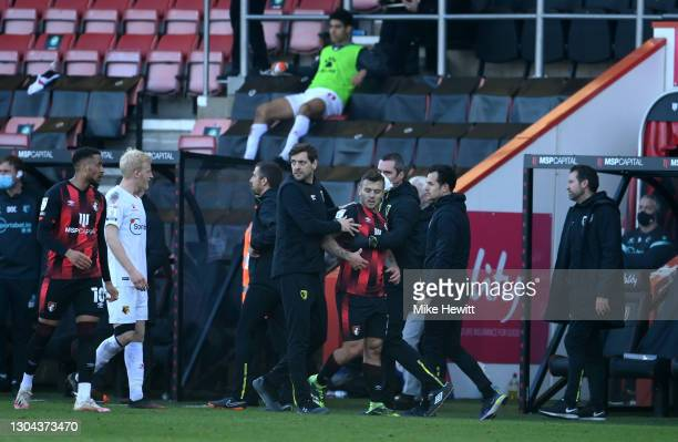 Jonathan Woodgate, Caretaker Manager of AFC Bournemouth holds back Jack Wilshere of AFC Bournemouth who reacts as he leaves the pitch after receiving...