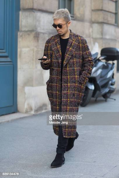 Jonathan Yee wears a Bottega Veneta coat and Carmina shoes outside the Balenciaga show at Place Vendome on January 18 2017 in Paris France