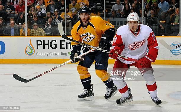 Jonathon Blum of the Nashville Predators skates against Damien Brunner of the Detroit Red Wings at the Bridgestone Arena on February 19 2013 in...