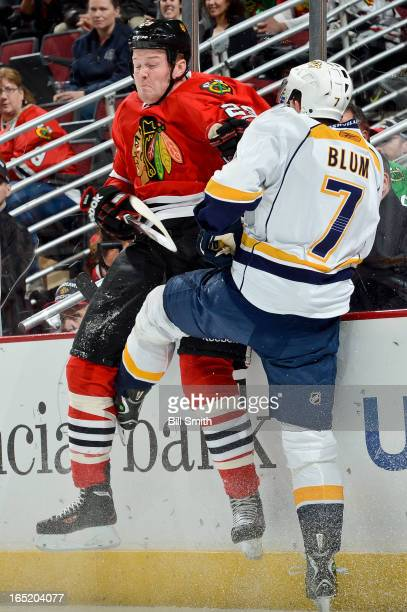 Jonathon Blum of the Nashville Predators slams Bryan Bickell of the Chicago Blackhawks into the boards during the NHL game on April 01 2013 at the...