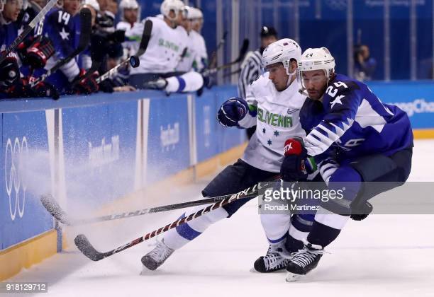 Jonathon Blum of the United States and Anze Kuralt of Slovenia collide during the Men's Ice Hockey Preliminary Round Group B game on day five of the...