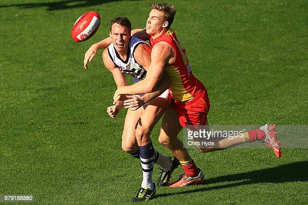 Jonathon Griffin of the Dockers handballs while tackled by Tom Lynch of the Suns during the round 18 AFL match between the Gold Coast Suns and the...