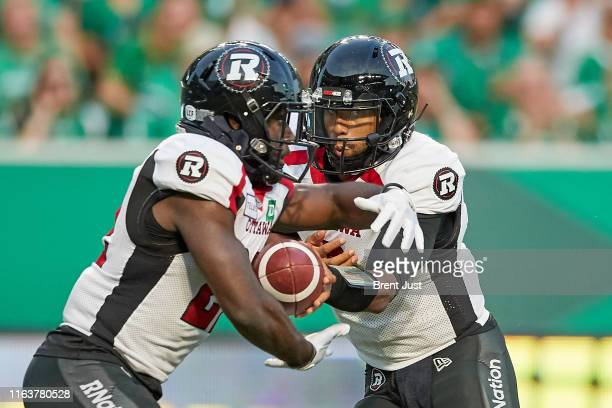 Jonathon Jennings hands the ball off to Greg Morris of the Ottawa RedBlacks in the game between the Ottawa RedBlacks and Saskatchewan Roughriders at...