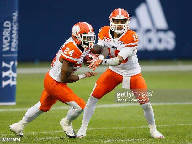 Jonathon Jennings hands the ball off to Jeremiah Johnson of the BC Lions during a CFL game against the Toronto Argonauts at BMO field on June 30 2017...
