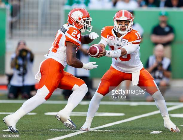 Jonathon Jennings hands the ball to Jeremiah Johnson of the BC Lions during the game between the BC Lions and the Saskatchewan Roughriders at Mosaic...