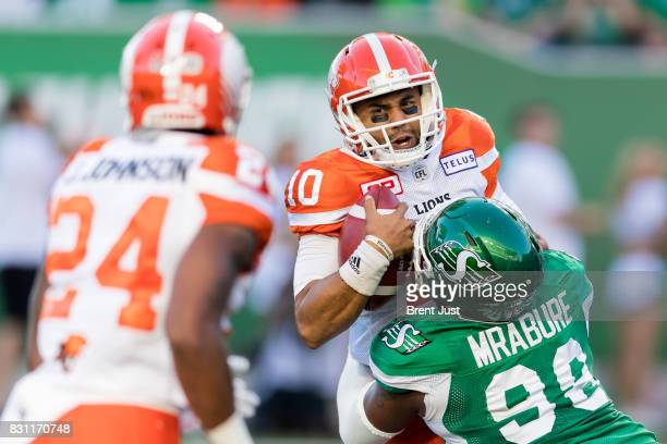 Jonathon Jennings of the BC Lions is sacked by Ese Mrabure of the Saskatchewan Roughriders in the first half of the game between the BC Lions and the...