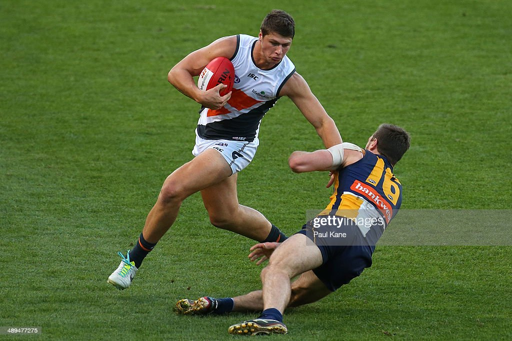 Jonathon Patton of the Giants avoids being tackled by Eric Mackenzie of the Eagles during the round eight AFL match between the West Coast Eagles and the Greater Western Sydney Giants at Patersons Stadium on May 11, 2014 in Perth, Australia.