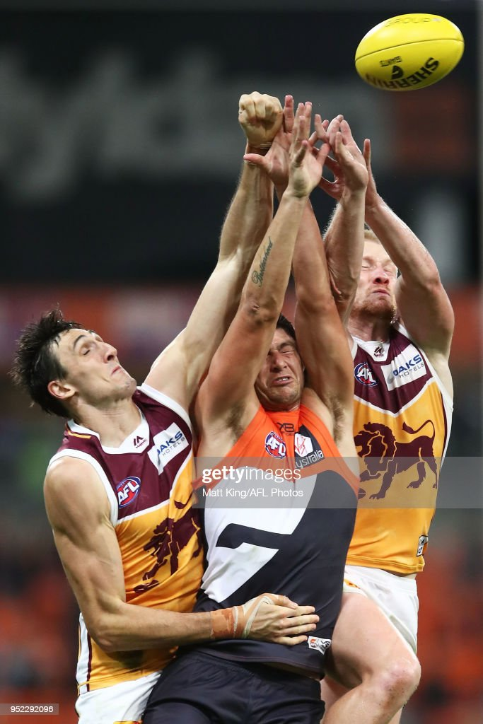Jonathon Patton of the Giants is challenged by Oscar McInerney and Nick Robertson of the Lions during the round six AFL match between the Greater Western Sydney Giants and the Brisbane Lions at Spotless Stadium on April 28, 2018 in Sydney, Australia.