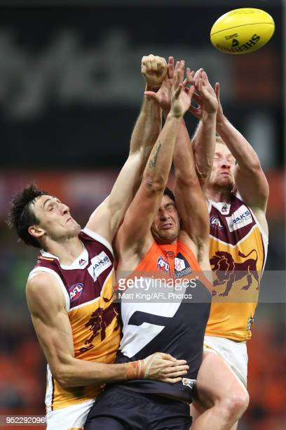 Jonathon Patton of the Giants is challenged by Oscar McInerney and Nick Robertson of the Lions during the round six AFL match between the Greater...