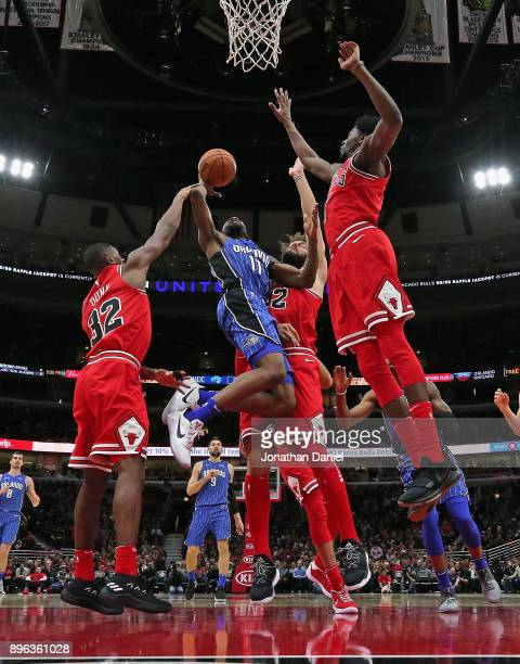 Jonathon Simmons of the Orlando Magic puts up a shot between Kris Dunn Robin Lopez and Justin Holiday of the Chicago Bulls at the United Center on...